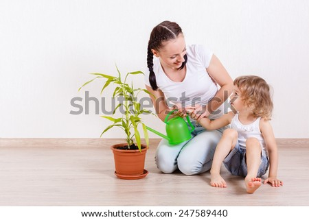 Happy mother and little daughter sit on the floor in a room and water the plant.