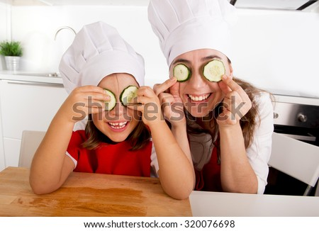 happy mother and little daughter wearing cook hat and red apron playing with cucumber slices on the eyes at home kitchen having fun in healthy nutrition and education concept - stock photo