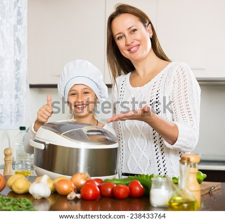 Happy mother and little daughter 9-10 years old using multicooker at kitchen - stock photo