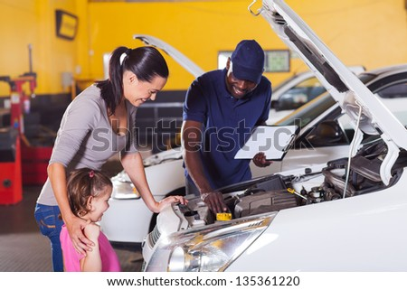 happy mother and little girl in car service center with auto technician - stock photo