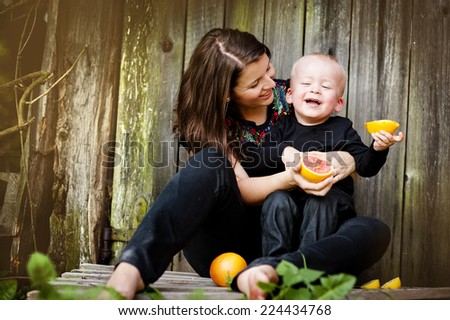 Happy mother and little son sitting by the wooden fence and eating orange - stock photo