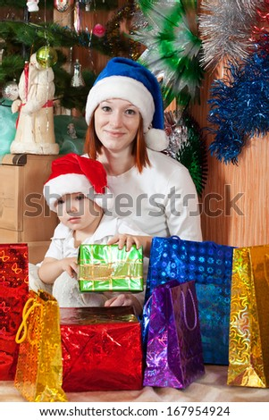 Happy mother and little son with Christmas gifts at home - stock photo