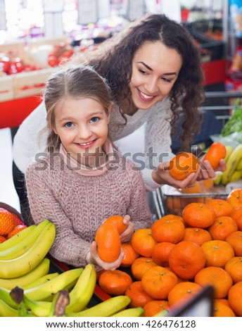 Happy mother and small cheerful daughter buying sweet citrus fruits