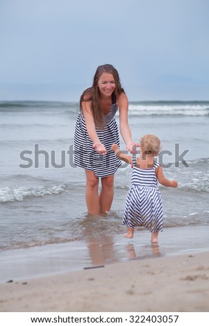 Happy Mother and small daughter go along the seashore, italy,