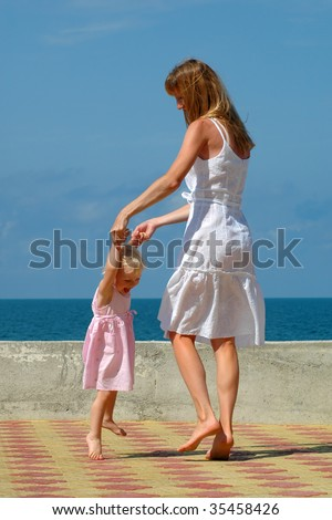 Happy mother and small girl dance
