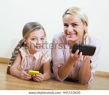 Happy mother and small girl playing with mobile phones indoor - stock photo