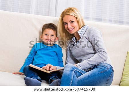 Happy mother and son are sitting on sofa and reading book together.Mother and son reading book together