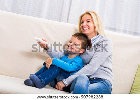 Happy mother and son are sitting on sofa and watching tv together.Family time