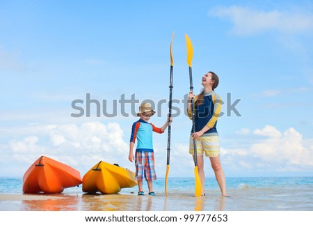 Happy mother and son at beach after kayaking