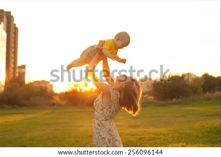 happy mother and son at sunset sunlight - stock photo