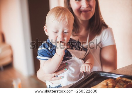Happy mother and son cooking at kitchen - stock photo