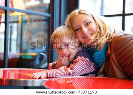 Happy mother and son in a Parisian cafe