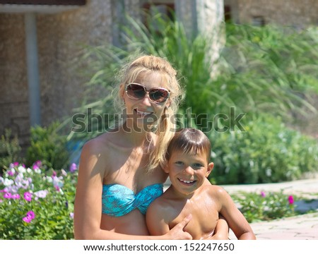 Happy mother and son in a spa hotel near pool