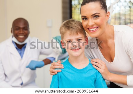 happy mother and son in dentist office - stock photo