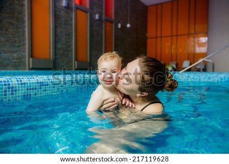 happy mother and son in the pool. playing sports. child development