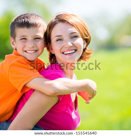 Happy mother and son in the spring meadow outdoor portrait - stock photo