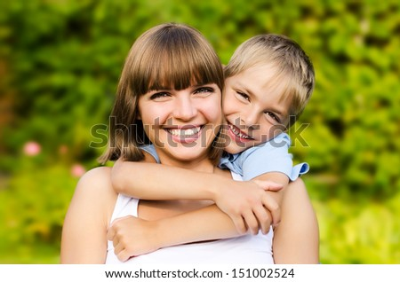 Happy mother and son laughing together outdoors