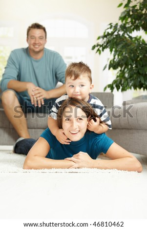 Happy mother and son lying on carpet at home, father watching from background.