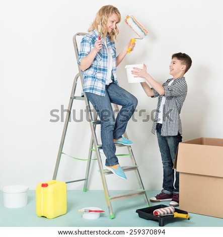 Happy mother and son makes repairs at home.