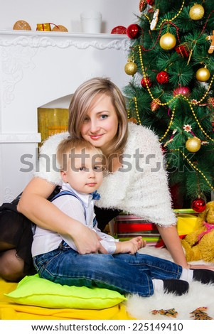 Happy mother and son near an decorated fir-tree for Christmas - stock photo