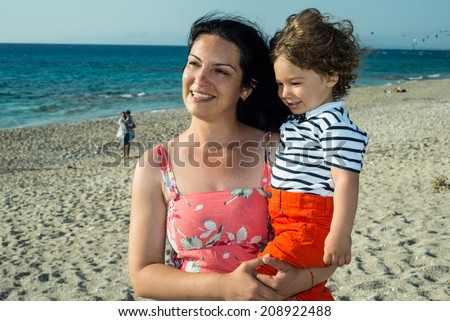 Happy mother and son on beach looking away to the sun - stock photo