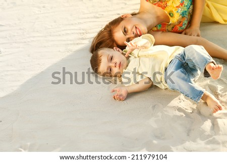 Happy mother and son on the beach sunset - stock photo