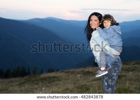 Happy mother and son piggyback in the mountains at sunset