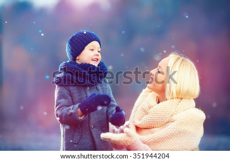 happy mother and son playing together under winter snow - stock photo
