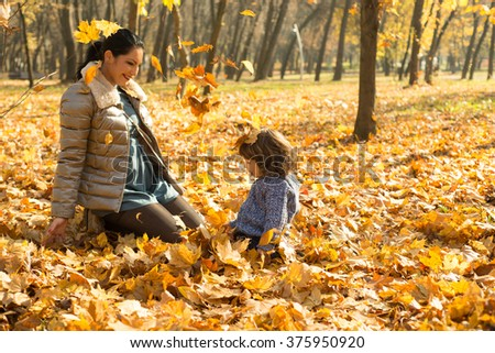 Happy mother and son playing with leaves in park and sitting down together