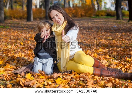 Happy mother and son sitting on autumn leaves and showing thumbs up. - stock photo