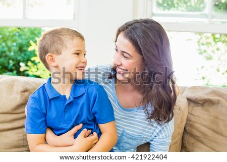 Happy mother and son sitting on sofa having fun in living room at home - stock photo