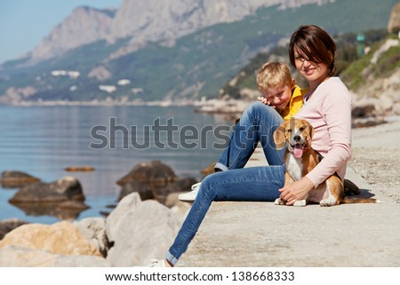 Happy mother and son sitting on the quay with beagle puppy