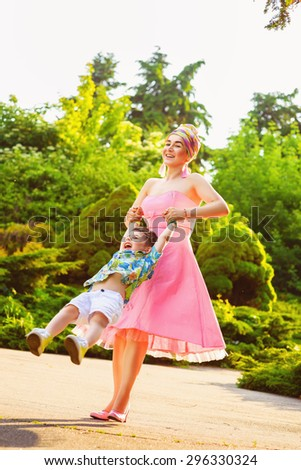 Happy Mother and son spinning in summer park - stock photo