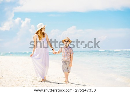 Happy mother and son walk along the white sand ocean beach having great family time on vacation on Pandawa Beach, Bali. Paradise, travel, vacation concept - stock photo