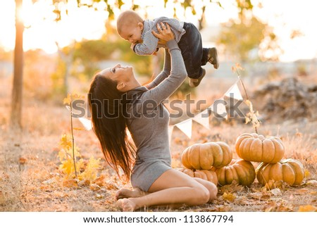 Happy mother and son with pumpkin on autumn leaves. Outdoor.