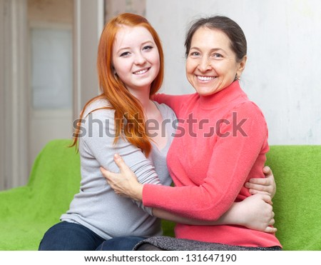 Happy mother and teenager daughter hugging each other in home interior - stock photo