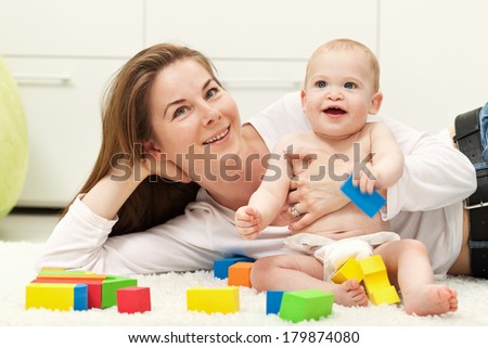 Happy mother and toddler boy playing together - stock photo