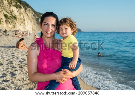 Happy mother and toddler son posing on Egremni beach in Greece - stock photo