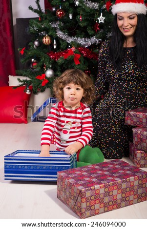 Happy mother and toddler son under Christmas tree opening gifts - stock photo