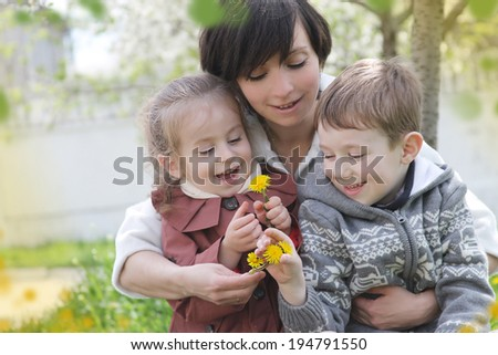 Happy mother and two children admiring spring garden - stock photo