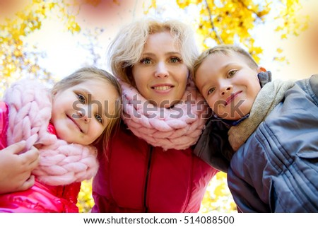 Happy mother and two children looking down in autumn