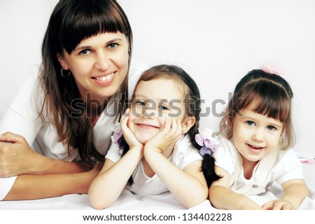 Happy mother and two daughters are on the floor - stock photo