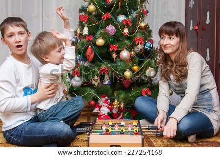 Happy mother and two her children playing near an decorated fir-tree for Christmas - stock photo