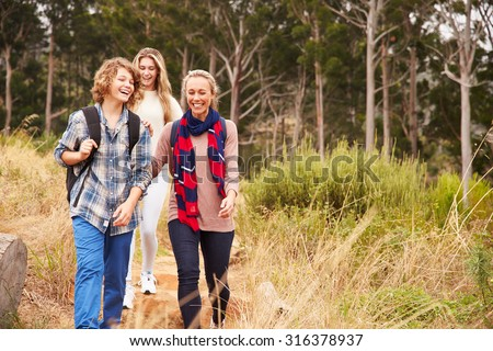 Happy mother and two kids walking in a forest