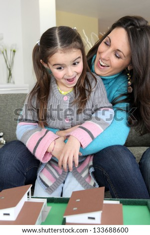happy mother and young daughter looking at house model - stock photo