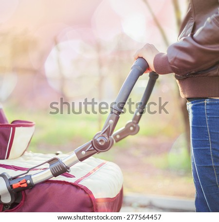 happy mother at outdoor wearing a spring jacket shakes a baby carriage