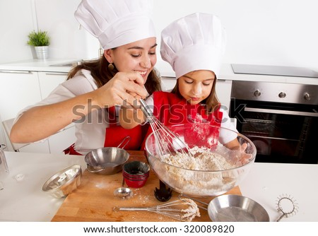 happy mother baking with little daughter in apron and cook hat working with flour , bowl and spoon preparing dough teaching the kid cooking and having fun together - stock photo