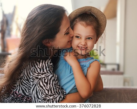 Happy mother cuddling and kissing her cute kid girl in hat - stock photo