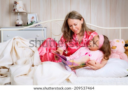 happy mother daughter reading a book at bedtime - stock photo