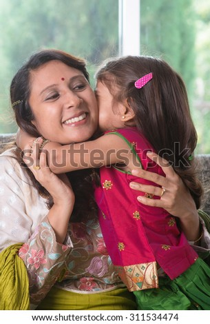 Happy Mother Day. Indian family at home. Asian girl kissing her mother, sitting on sofa. Parent and child indoor lifestyle.
